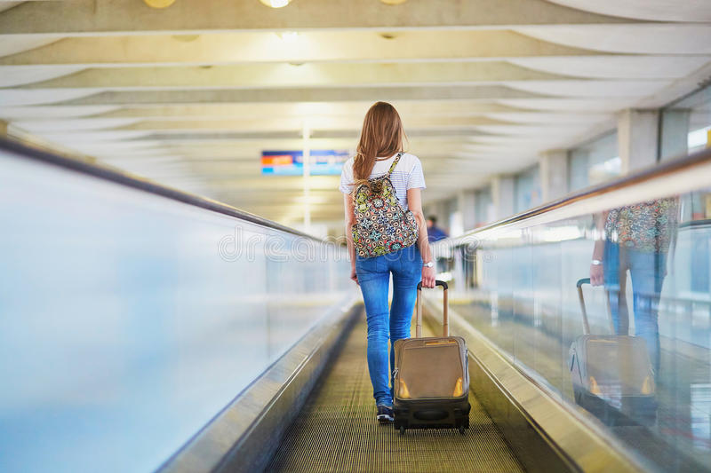 Download Tourist Girl With Backpack And Carry On Luggage In International Airport, On Travelator Stock Photo - Image of shirt, girl: 83723890