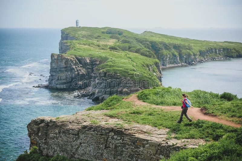 Tourist girl with a backpack in the wild of the Primorye Far East of Russia, Russky Island, Cape Tobizina royalty free stock images