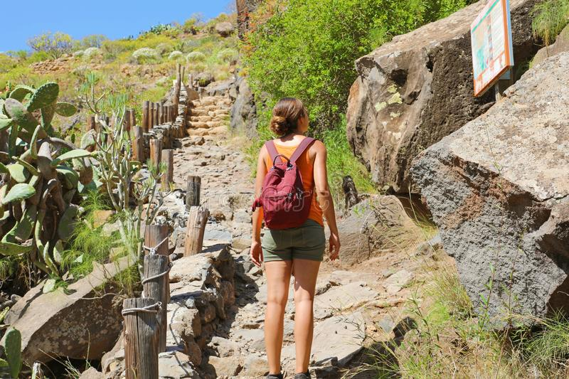 Tourist girl backpacker reading map on the tourist path in Tenerife, Canary Islands, Spain.  stock photography