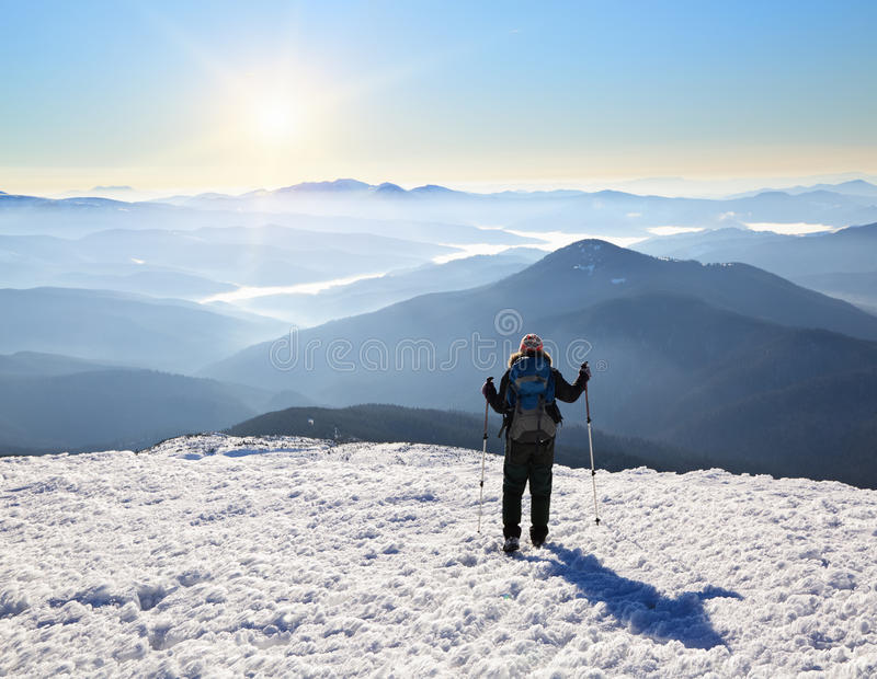 A tourist girl is going towards the sun ang high mountains. royalty free stock photography