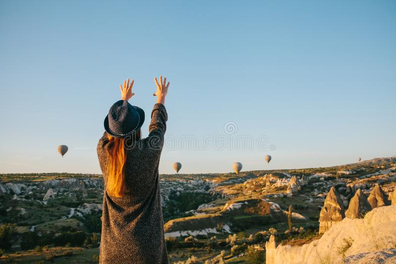 A tourist girl in a hat admires hot air balloons flying in the sky over Cappadocia in Turkey. Impressive sight. Tourism stock photos