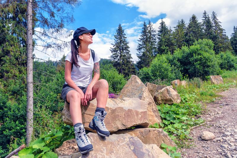 Tourist girl in hiking boots on the rock stock photo