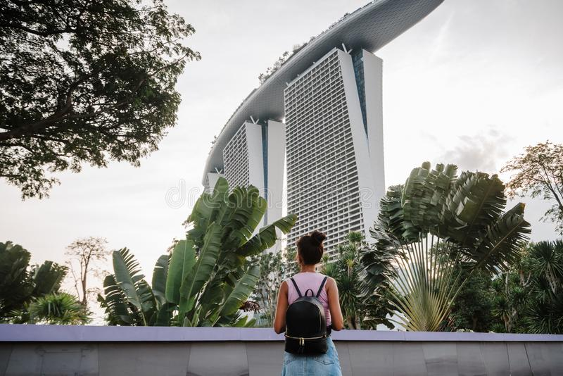 Tourist girl is impressed by the beautiful view of the modern city. Cityscape of the Asian metropolis. Modern buildings and. Structures. Singapore. Marina Bay royalty free stock images