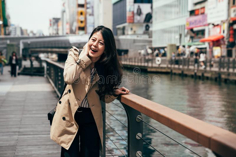 Tourist girl laughing relying on the handrail. Near the river in dotonbori osaka japan on sunny day. young local japanese woman cheerfully having fun beside the royalty free stock photos