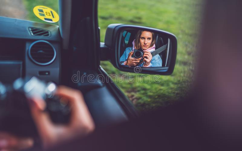 Tourist girl in an open window of a car taking photography click on retro vintage photo camera, photographer looking on reflection royalty free stock photography