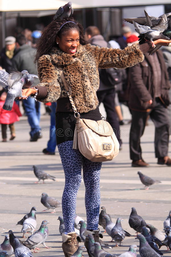 Tourist girl with pigeons stock image