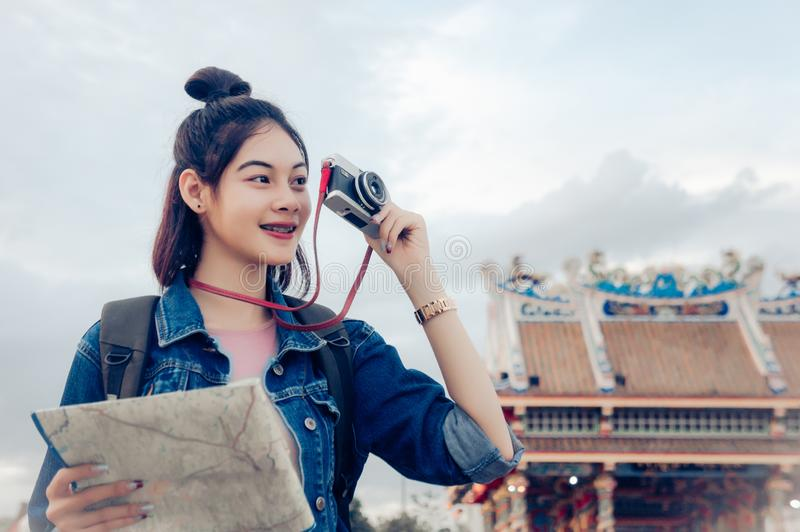 Tourist girl`s hold a map and looking at view Travel location Cultural and smiling on the day trip.  royalty free stock photo
