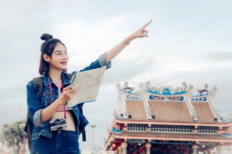 Tourist girl`s hold a map and looking at view Travel location Cultural and smiling on the day trip.  stock photography