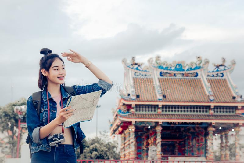 Tourist girl`s hold a map and looking at view Travel location Cultural and smiling on the day trip.  stock photo