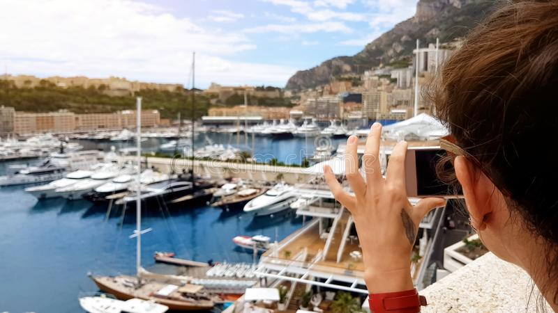 Tourist girl taking photo of yachts in Mediterranean sea port, using smartphone royalty free stock image