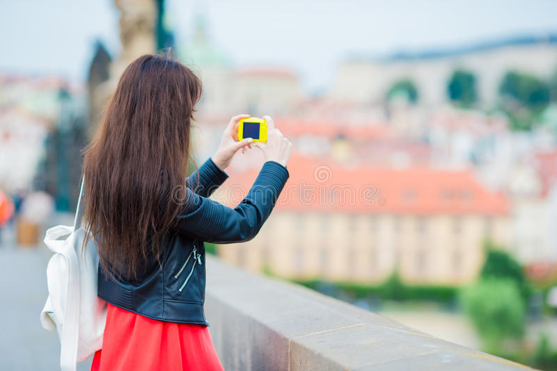 Tourist girl taking travel photos by famous attraction with smartphone on summer holidays. Young attractive tourist stock photo