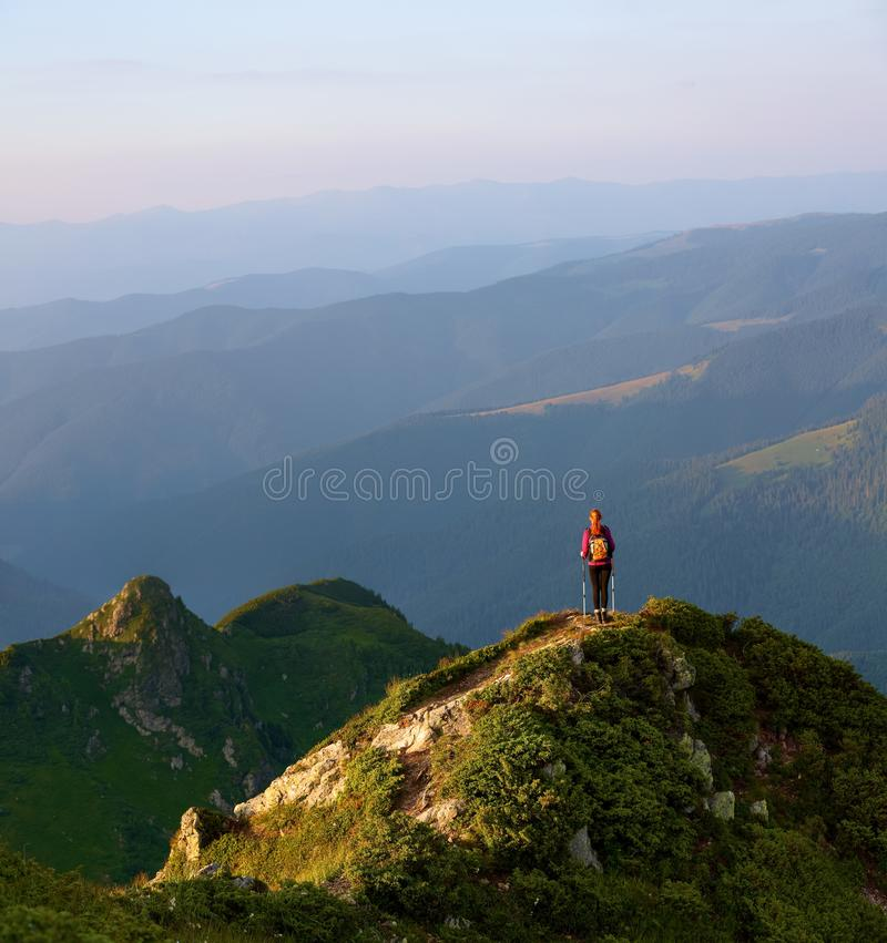 The tourist girl with the tracking sticks and the back sack at the edge of the cliff. The landscape with the high mountains. royalty free stock image