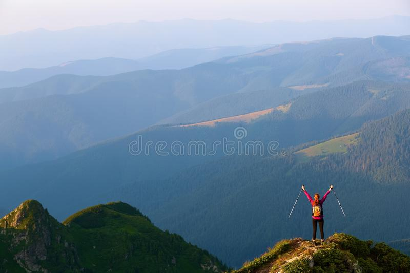 The tourist girl with the tracking sticks and the back sack at the edge of the cliff. The landscape with the high mountains. royalty free stock photography
