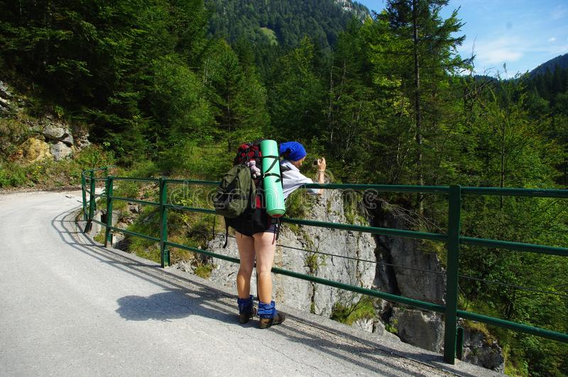 Tourist girl with two backpacks photographing the landscape royalty free stock images