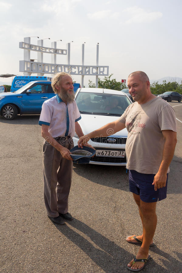 Tourist gives alms to a bearded man the beg with the hat in the Parking lot at the entrance to the city stock photo