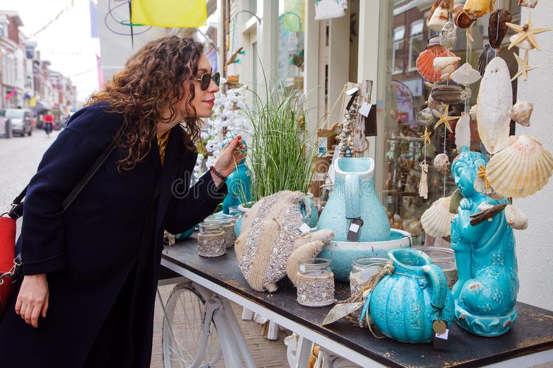 Young woman shopping street market glasses coats curly hair brunette blue vase sea shells choose stock photos