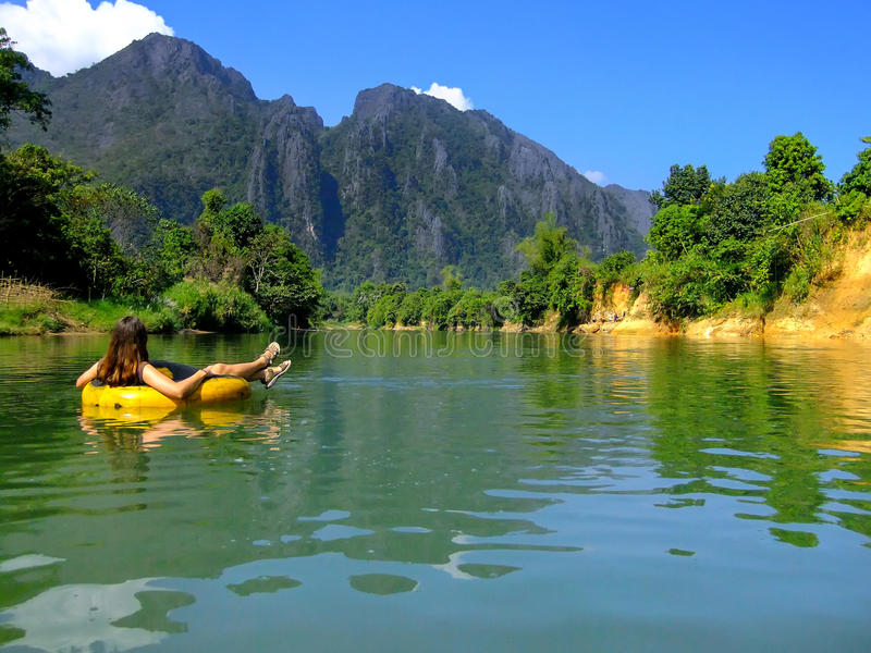 Tourist going down Nam Song River in a tube surrounded by karst. Scenery in Vang Vieng, Laos. Tubing is a popular tourist activity in Vang Vieng stock photography