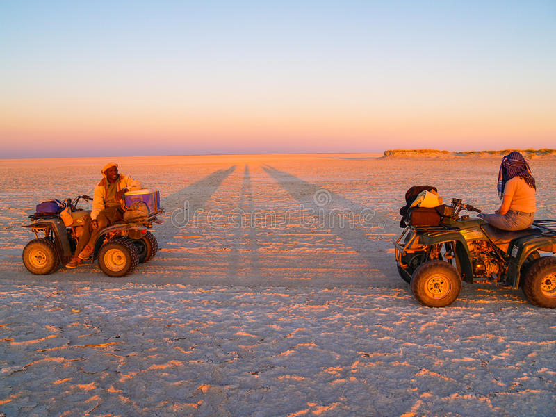 Tourist and guide on quad bikes stop while crossing Makgadikgadi Pans National Park, scenic large flat area of salt pan desert t stock photos