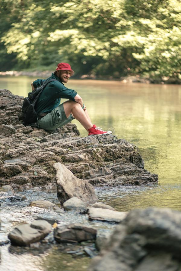 Tourist guy with backpack sitting near lake in a wild summer wood. Expedition. Exploring and expedition concept. Bearded caucasian tourist male sitting on the stock photos