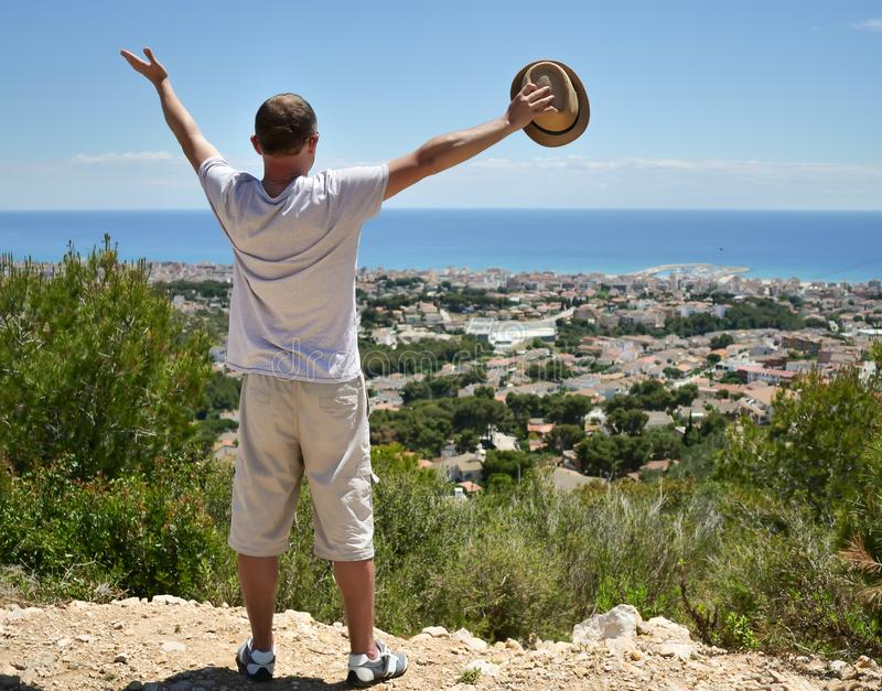 Tourist guy stands on top of a hill spreading his arms wide to the side, holds hat concept of travel, freedom. Tourist guy stands on top of a hill spreading his stock image