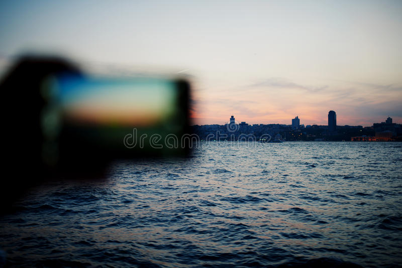 Tourist hand holding cell phone while taking a photograph of city panorama in travel. Person taking a photo of amazing sunset using smart phone camera, tourist stock images