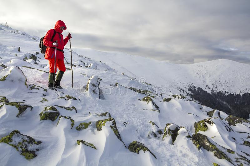 Tourist hiker in bright red clothing with walking sticks descend. Ing dangerous rocky mountain slope covered with snow on stormy cloudy sky copy space background stock images