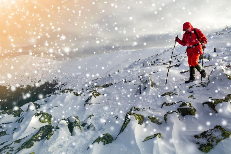 Tourist hiker in bright red clothing with walking sticks descend. Ing dangerous rocky mountain slope covered with snow on stormy cloudy sky copy space background stock photos