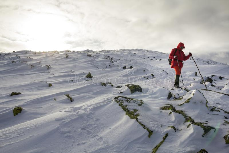 Tourist hiker in bright red clothing with walking sticks descending dangerous rocky mountain slope covered with snow on stormy. Cloudy sky copy space background stock photo