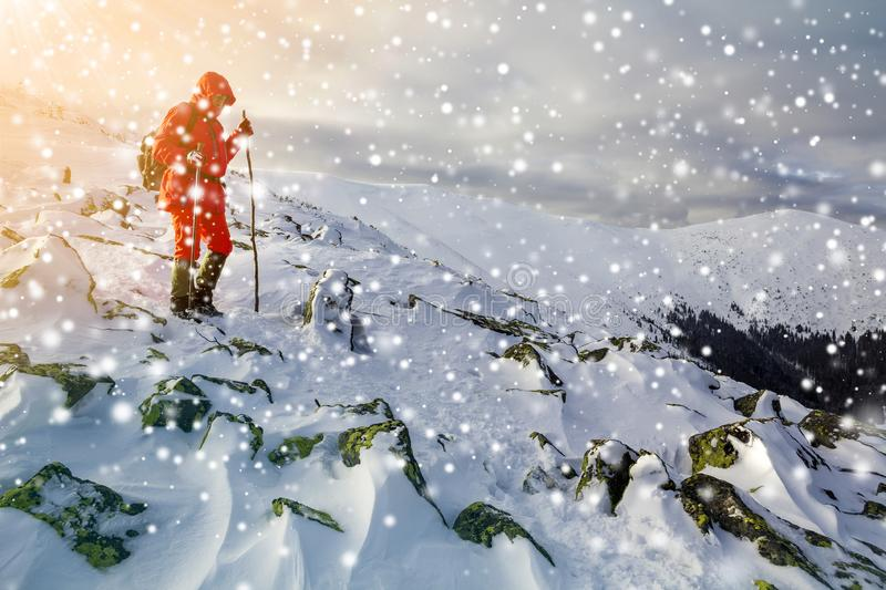 Tourist hiker in bright red clothing with walking sticks descending dangerous rocky mountain slope covered with snow on stormy. Cloudy sky copy space background stock image