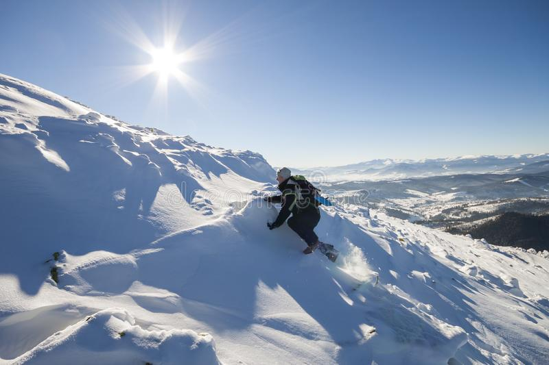 Tourist hiker climber in winter clothing with backpack climbing dangerous rocky steep mountain slope covered with deep snow, white. Sun rays shining in bright royalty free stock image