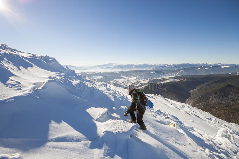 Tourist hiker climber in winter clothing with backpack climbing dangerous rocky steep mountain slope covered with deep snow, white. Sun rays shining in bright royalty free stock photos