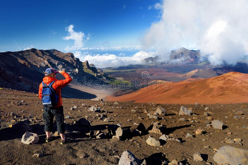 Tourist hiking in Haleakala volcano crater on the Sliding Sands trail. Beautiful view of the crater floor and the cinder cones bel stock images