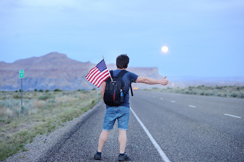 Tourist hitchhiking along a desolate road. Middle age male tourist with american flag in backpack hitchhiking along a desolate road royalty free stock photo