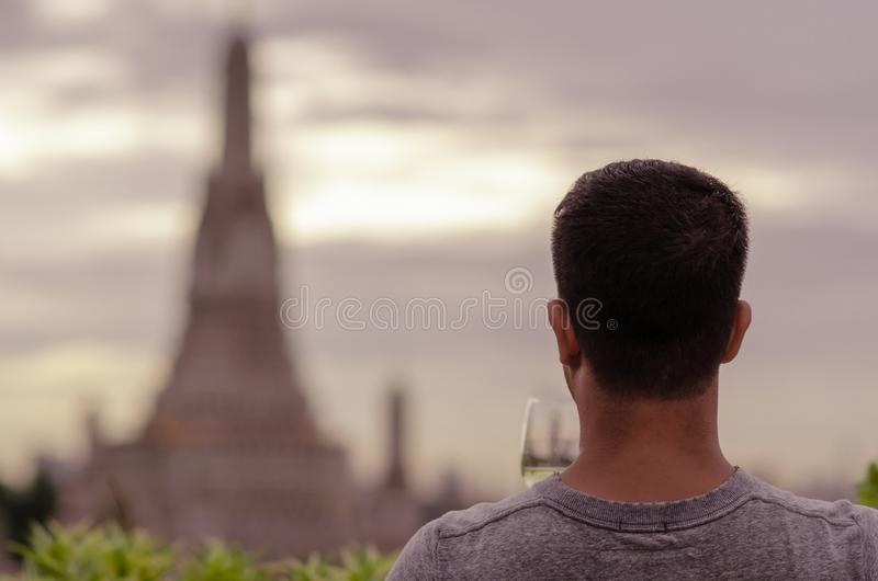 A tourist holding a glass of white wine looking at blurred background of temple stock photo