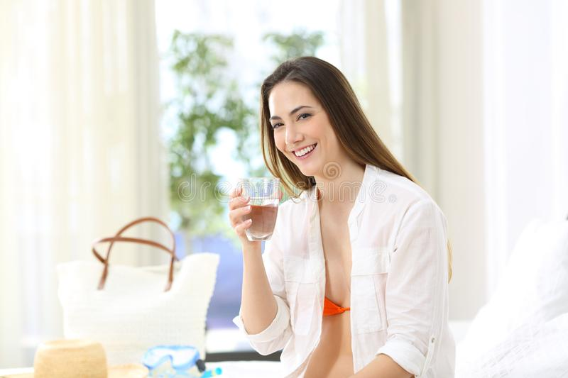 Tourist holding potable tap water in an hotel. Happy tourist holding potable tap water in an hotel room during a travel on summer vacations stock image