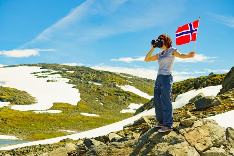 Tourist holds camera and norwegian flag in mountains royalty free stock images