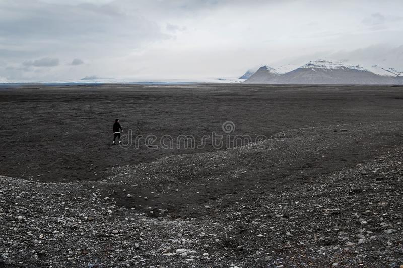 Tourist jumps over rocks in Iceland royalty free stock photo