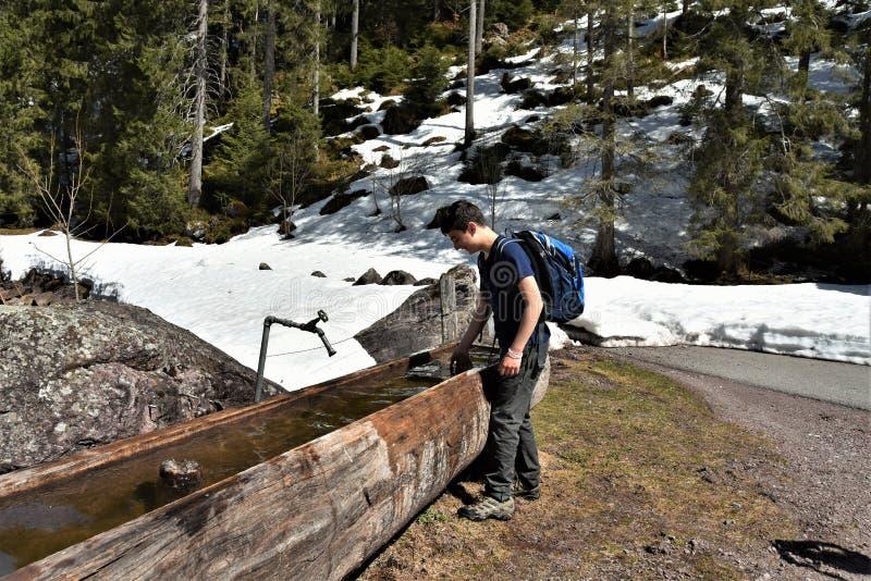 Tourist Junge spielt mit dem Wasser in der hölzernen Wassertrog in der Nähe des Touristenwegs direkt in Richtung Murg Seen stockfotografie