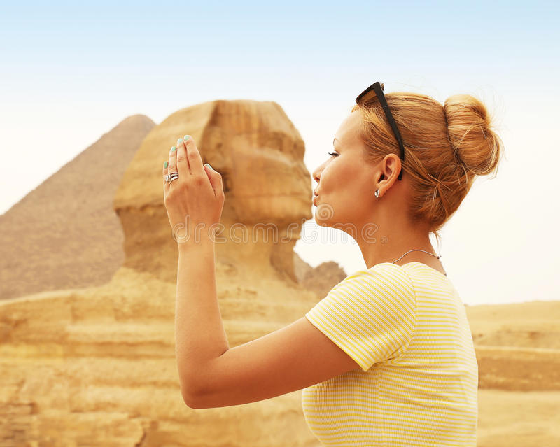 Tourist kissing the Sphinx, Cairo, Egypt. Kiss of the Sphinx. Young Blonde Woman in Giza royalty free stock photo
