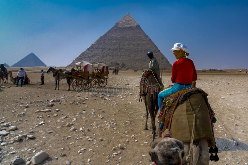 Tourist Leslie Plimpton fährt Kamel vor den Großen Pyramiden Ägyptens lizenzfreies stockbild
