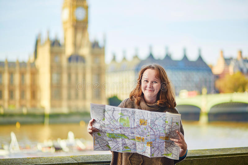 Tourist in London near Big Ben with map. Tourist in London near Big Ben looking for direction using map stock photo