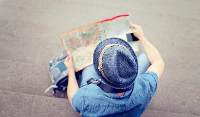 Tourist looking on the city map - Backpack concept - View from the top - Focus on the hat.  royalty free stock photo