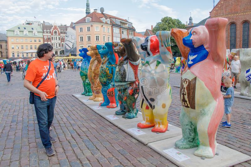 The tourist looking at the colorful bears at the international art exhibition United Buddy Bears. The bear circle was. Riga Latvia 12 July 2018. The tourist stock photography