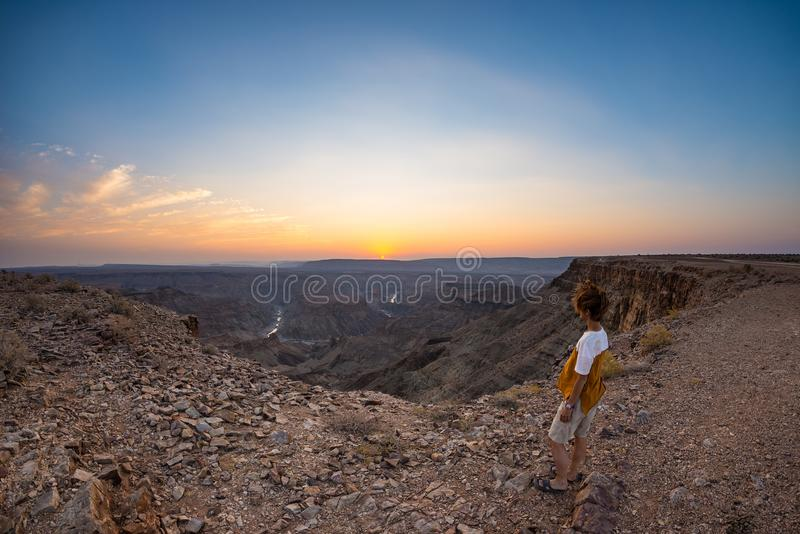 Tourist looking at the Fish River Canyon, scenic travel destination in Southern Namibia. Ultra wide angle view from above, colorfu. L scenic sunset royalty free stock photo