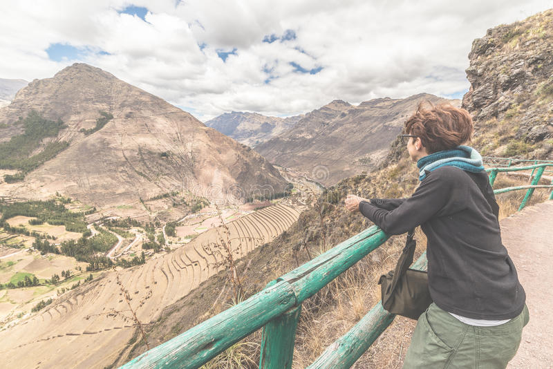Tourist looking at Inca terraces of Pisac, Peru, filtered image. Tourist looking at the majestic Inca terraces of Pisac, Sacred Valley, major travel destination royalty free stock images