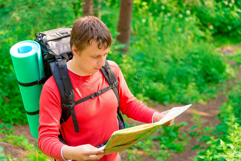 Tourist is looking for its location. On the map stock photo