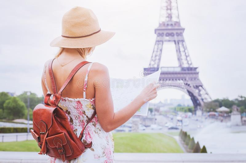Tourist looking at the map of city Paris near Eiffel tower stock photo