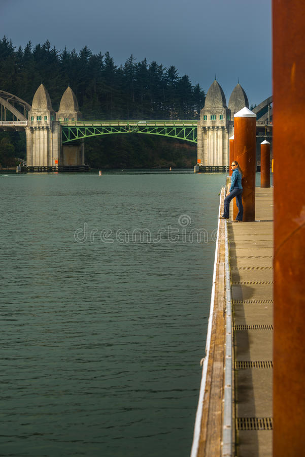 Tourist looking at Siuslaw River from the Florence Marina Oregon stock images