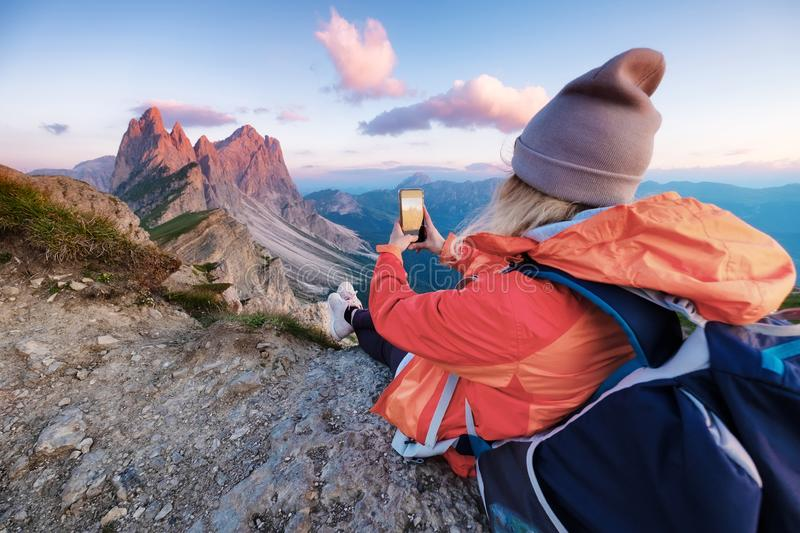 Tourist make a photo by a phone on the high mountain top. People traveling in the mountains. Dolomite Alps, Italy stock image