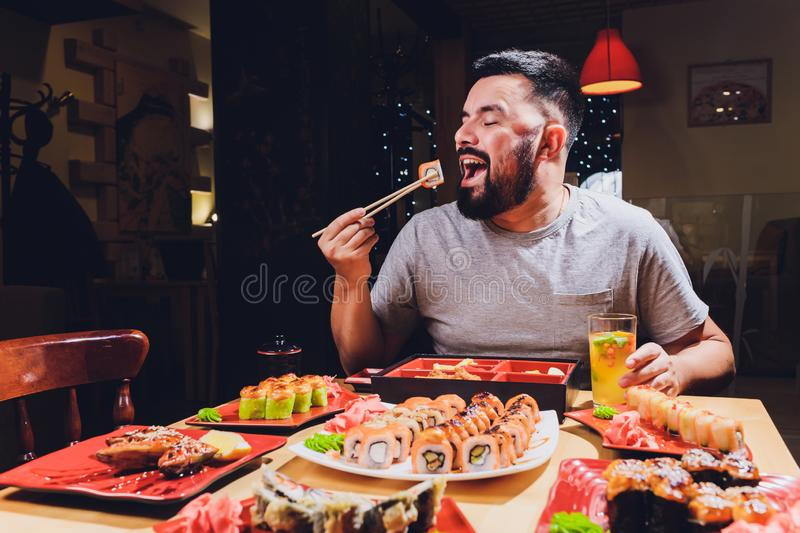 Tourist man eating asian food street local cafe, smile using chopstick. Tourist man eating asian food street local cafe, smile using chopstick royalty free stock photography